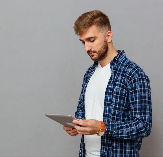 portrait-of-a-man-using-tablet-computer-PCDLD3R3-min